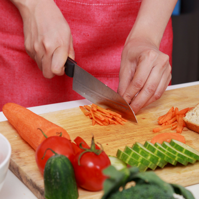 Easy Meal Prep Tips to Save Time in the Kitchen - Whole Family Living. Person's hands cutting up vegetables on cutting board.