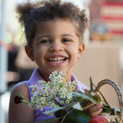Great Reasons to Eat Local, Seasonal Foods - Whole Family Living. Little girl holding basket of fresh flowers at a farmer's market.
