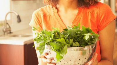 Simple Ways to Develop Healthy Eating Habits - Whole Family Living. Young woman holding colander full of healthy, leafy green vegetables.