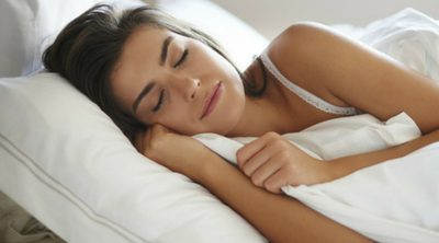 Getting Adequate Sleep to Maintain Good Health - Whole Family Living. Woman sleeping in bed.