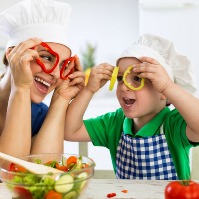 Healthy Eating for Busy Families Made Easy. Mother and son having fun cutting up veggies in the kitchen.