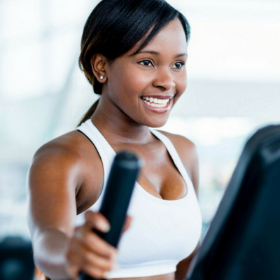 Creat an Exercise Routine to Lower Stress. Woman smiling as she works out on an elliptical machine at the gym.