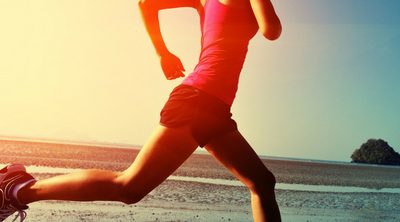 Setting Healthy Weight Loss Goals for the New Year and Beyond. Woman exercising; jogging on the beach at sunrise.