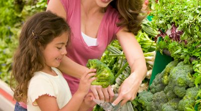 Simple Ways to Start Eating Healthy at Home. Mother and daughter shopping for healthy food in the produce section of the grocery store.