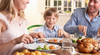 5 Simple Tips to Plan Healthy Family Meals. Family of four eating a healthy dinner at dining table.