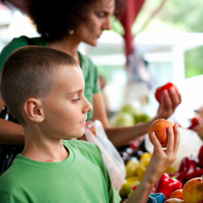 Guide to Buying Local, Seasonal Produce - Whole Family Living. Boy and mother shopping for produce at farmer's market.