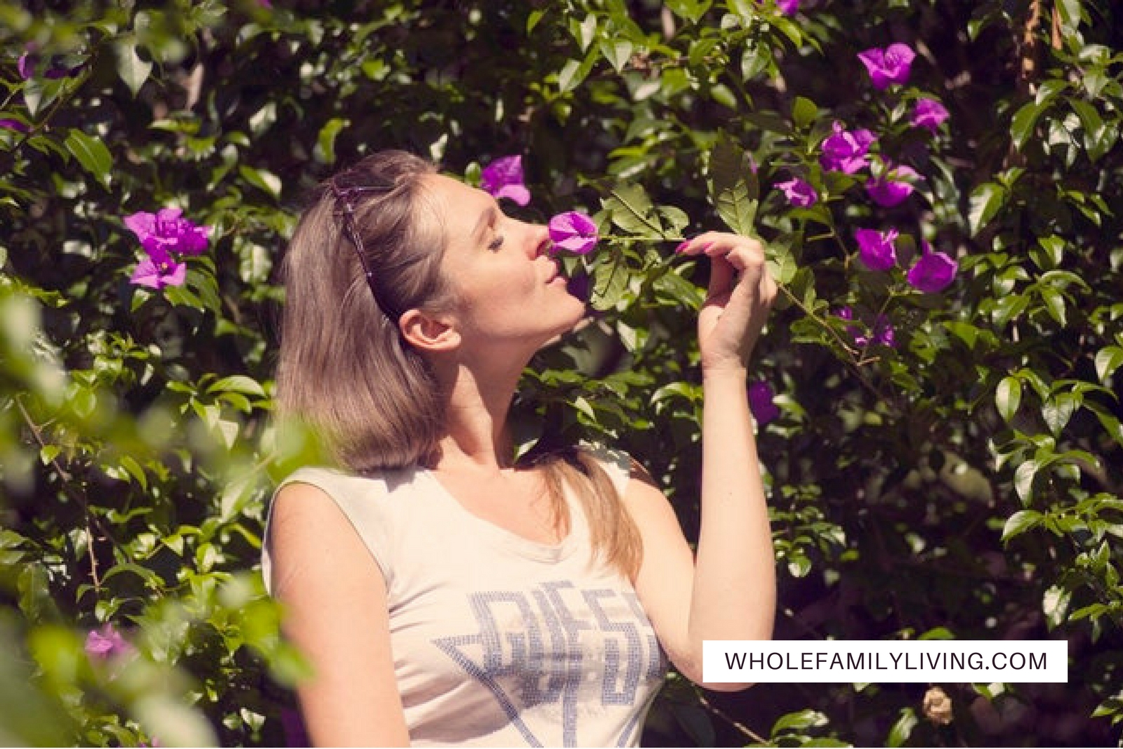 8 Ways to Start Simplifying Life Today. Woman standing outside smelling a purple flower.