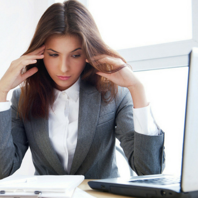 Common But False Beliefs About Stress - Whole Family Living. Woman in corporate setting with hands on head.