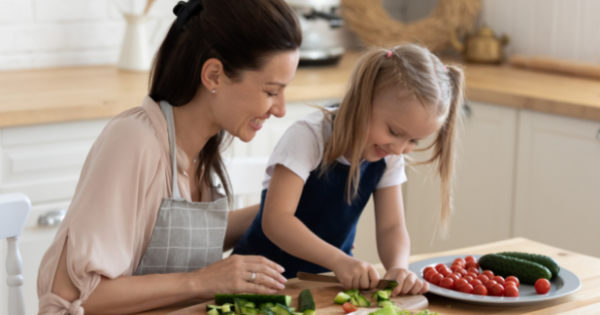 Mom and daughter cooking, chopping vegetables in the kitchen at home. Encourage kids to develop healthy eating habits.