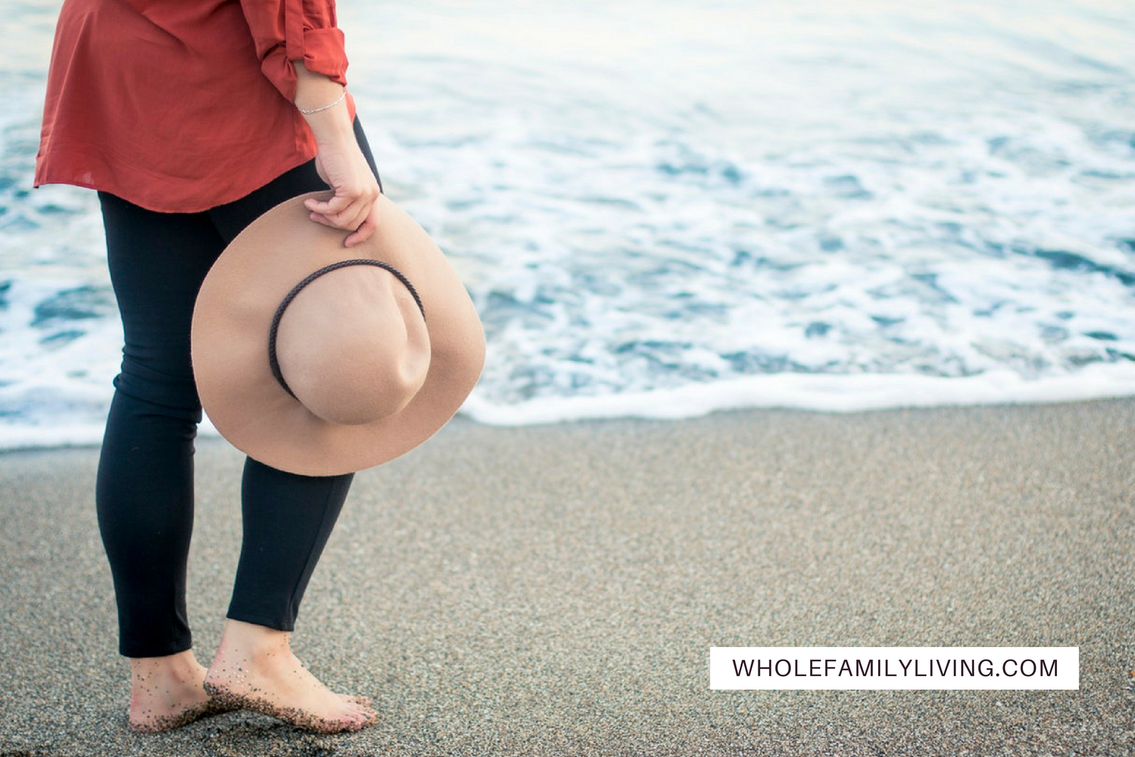 How to Simplify Your Life to Reduce Stress. Woman walking barefoot on the beach holding a hat.
