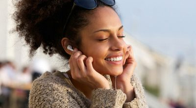 Easy Ways to De-stress When Life Gets Busy. Young woman outside listening to music on headphones.