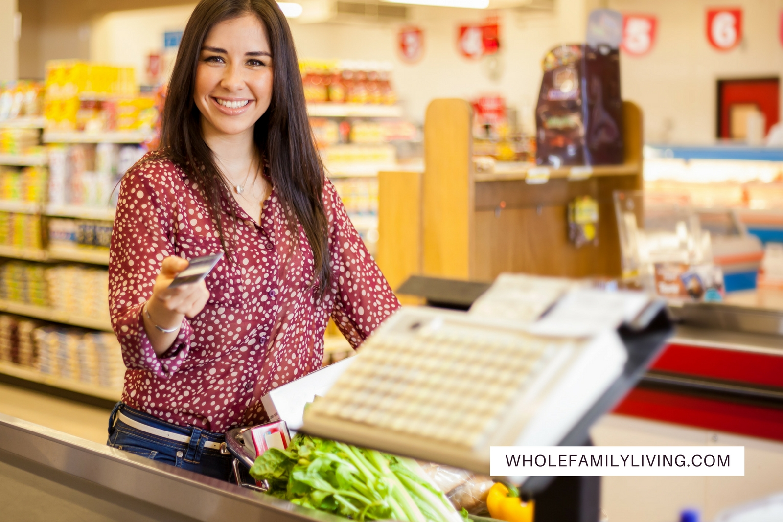 Avoid These Common (and Costly) Mistakes at the Grocery Store. Woman in supermarket paying for groceries.