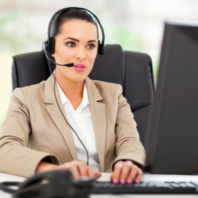 Woman sitting at a desk wearing a headset and typing on the computer keyboard while talking to a customer. Health Risks of Sitting All Day at Work - Whole Family Living