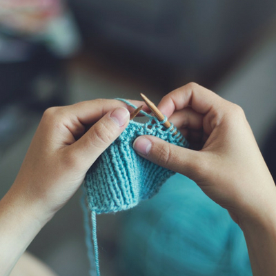 Best hobbies for stress relief after a busy day at work. Person knitting with blue yarn.
