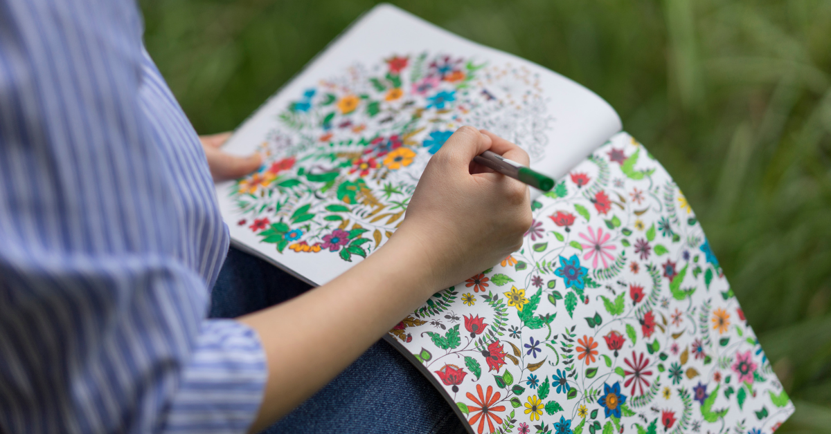 person sitting in the grass coloring in an adult coloring book