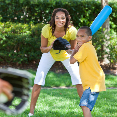 Routines Proven to Simplify Family Life. Young boy practicing softball swing outside with parents.