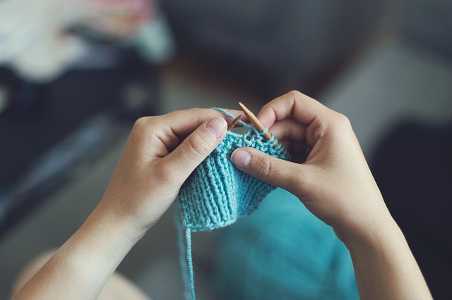 person knitting with blue yarn