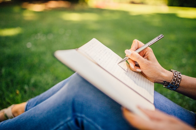 Woman sitting in the grass while writing in a journal to relieve stress. My Fit Habits