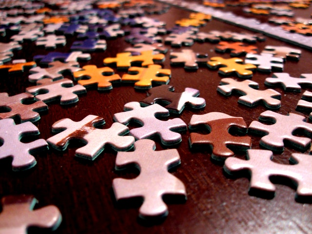 Puzzle pieces on a table. Do puzzles to relieve stress after work. My Fit Habits