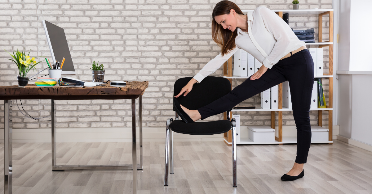 Woman stretching leg on a chair at the office. Using app to set reminders to stand and take a stretch break at work.