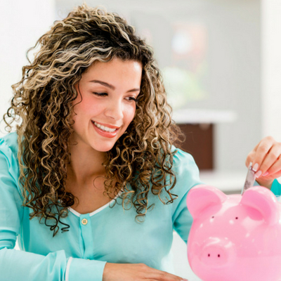 Easy Ways to Conquer Your Financial Fears - Whole Family Living.com. Woman smiling while looking at a pink piggy bank.