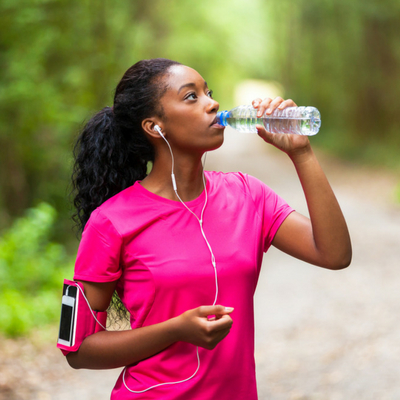 Easy Ways to Start Improving Your Health Today. Young woman taking a break from exercising to drink water.