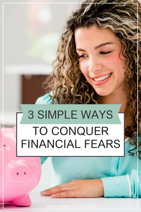 Easy ways to conquer financial fears. Woman smiling while looking at a pink piggy bank.