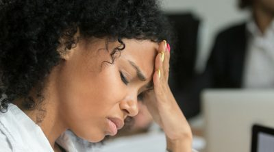 How to Reduce Anxiety at Work - woman in office meeting with eyes closed and hand on head