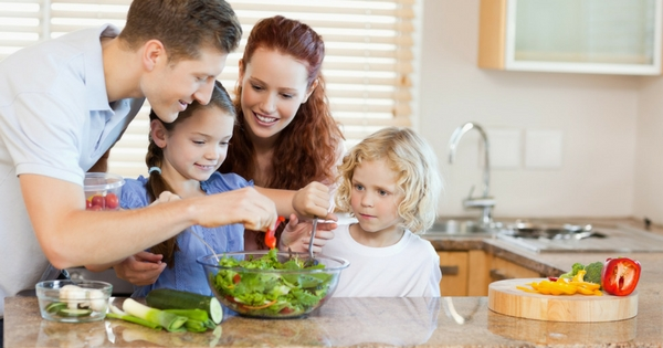 Family of four preparing a healthy meal together in the kitchen. Encourage kids to eat healthier meals at home.