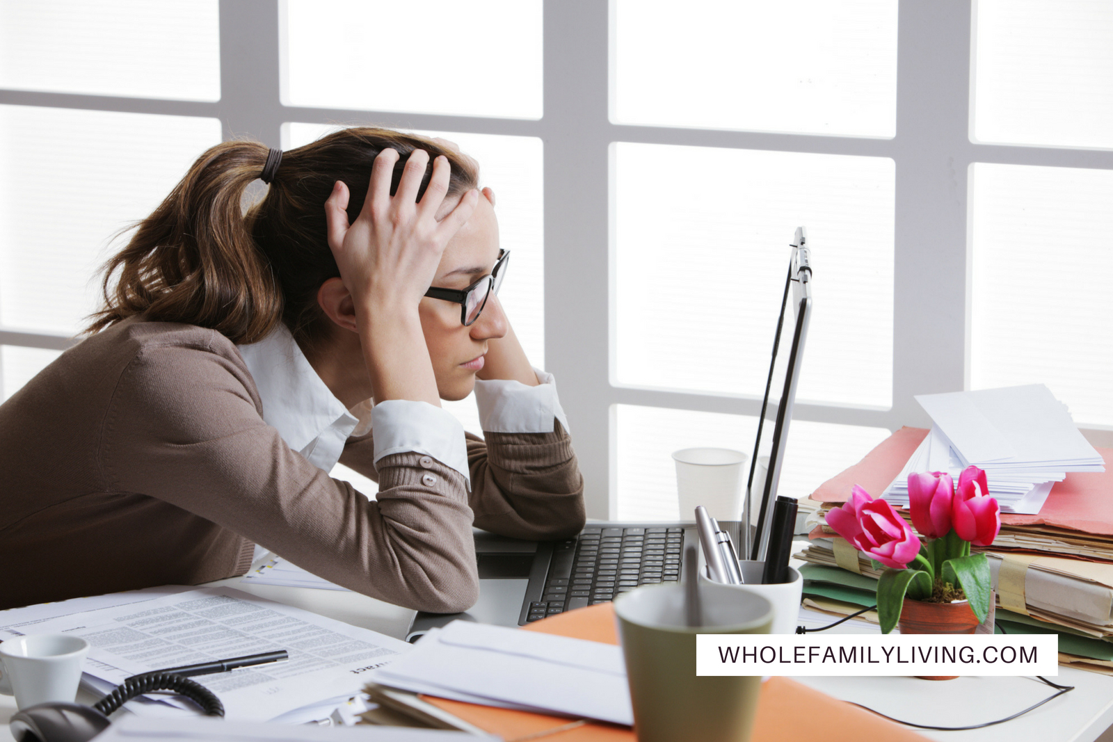 How to Manage Stress at Work. Female employee talking on the phone with piles of paperwork on her desk.