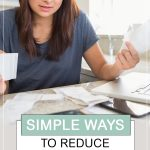 Simple Ways to Reduce Stress Over Money. Woman sitting at table with computer looking at bills.
