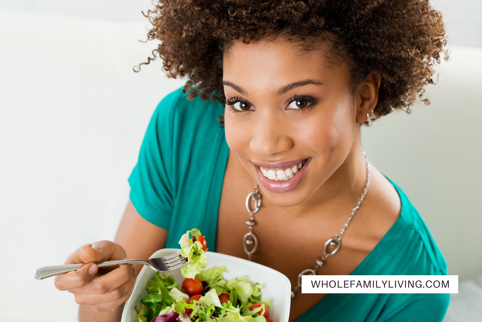 Tips to Start a Mindful Eating Practice. Attractive African-American woman with natural hair eating a healthy salad.