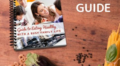Guide to Eating Healthy with a Busy Family Life - Whole Family Living. Healthy Eating Guide laying on wood table with healthy groceries.