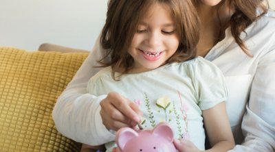 Steps to Improve Your Family's Financial Well-being - Whole Family Living. Mother and daughter looking at piggy bank.