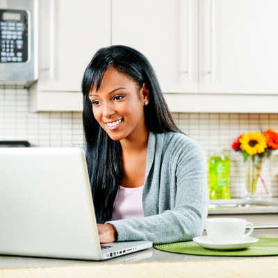 Iron-clad Strategies to Conquer Your Goals This Year. Smiling woman sitting at kitchen table working on laptop.