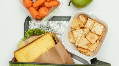 Simple Tips for Eating Healthy on the Go - Whole Family Living. Green lunch bag with assortment of healthy snacks.
