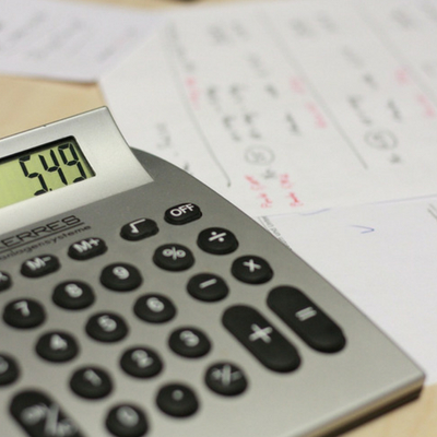 Smart Ways to Cut Your Family's Monthly Expenses - Whole Family Living. Calculator on desk with bills.