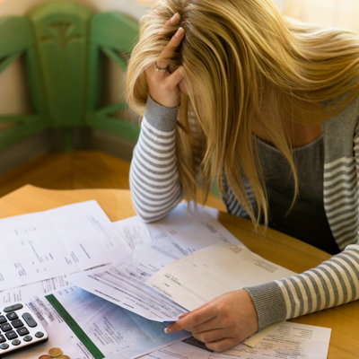10 Steps to Reduce Financial Stress and Start Living Your Life - Whole Family Living. Woman sitting at desk looking at stack of bills.