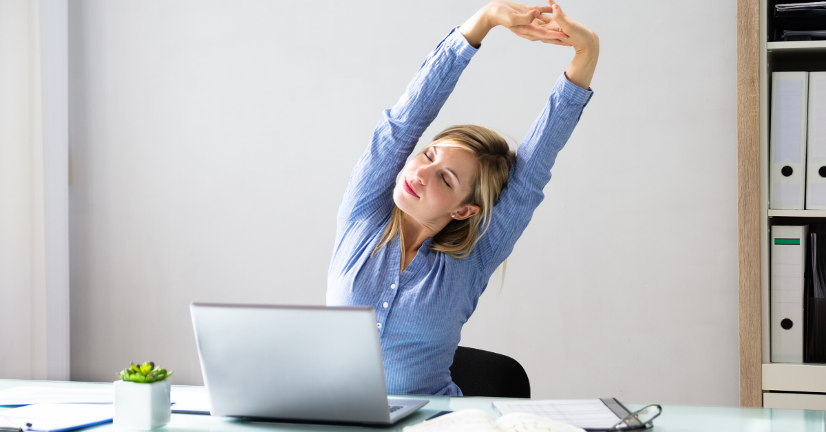 Woman in the office stretching at her desk. Apps to Help You Move More at Work - Whole Family Living