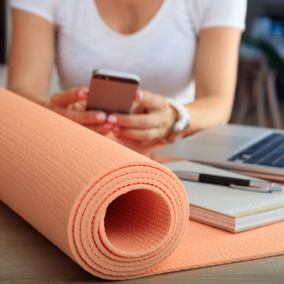 Woman sitting at desk on her lunch break with a peach yoga mat. Activity and Break Reminder Apps to Help You Move More at Work - Whole Family Living