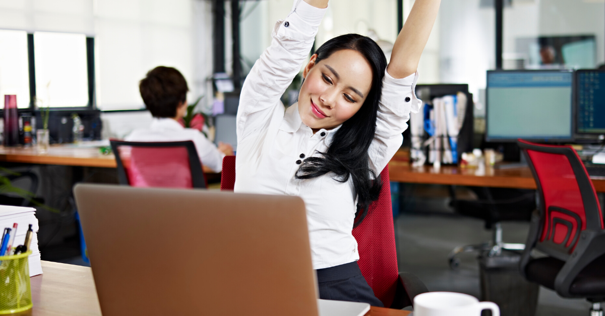 Woman taking a stretch break at her desk. 5 Types of Apps to Help You Stay Healthy at Work - Whole Family Living