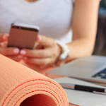 Woman on break with exercise mat. Apps to Help You Stay Healthy at Work - Whole Family Living