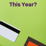 Top view of a notebook and credit card on a desk with a green background. 7 Steps to Conquer Your Goals This Year (Without Resolutions) - Whole Family Living