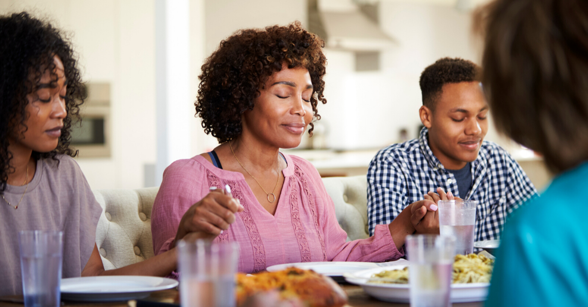 Family saying grace at family mealtime. How to Get Your Family Excited About Mealtime - Whole Family Living