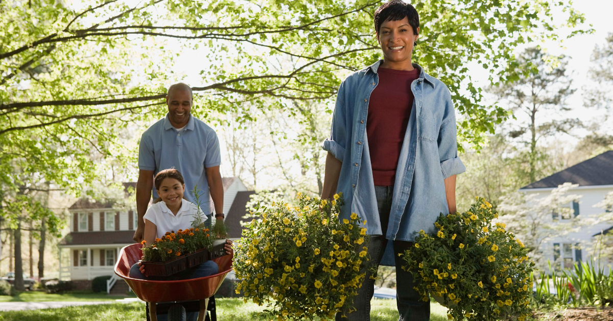 Family outside doing yardwork together. 17 Examples of Family Goals to Work on This Year - Whole Family Living