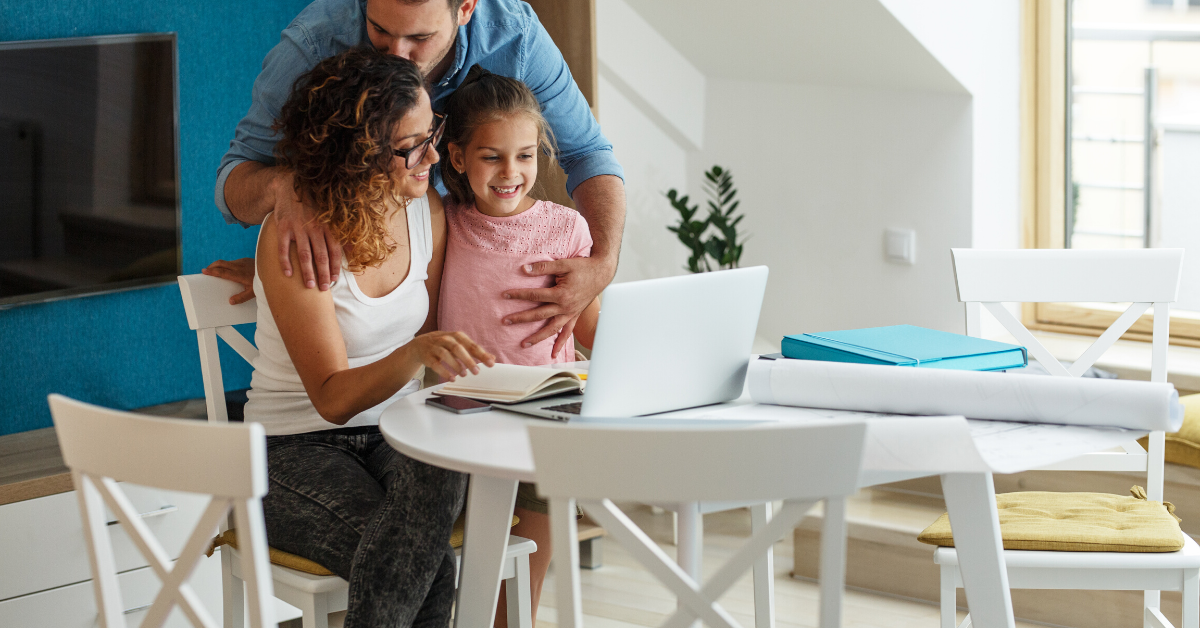 Family sitting at a table reviewing budget and savings. 17 Examples of Family Goals to Work on This Year - Whole Family Living