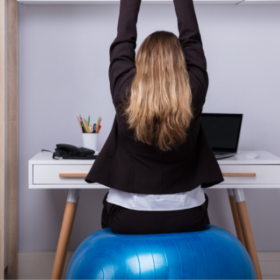 Woman sitting on a balance ball while working at her desk. Best Exercise Equipment to Keep at the Office - Whole Family Living