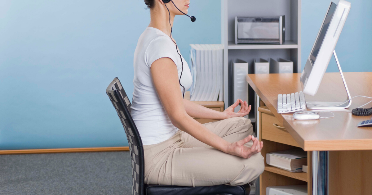 Woman in yoga pose at her desk. Stay healthy while working from home. Whole Family Living