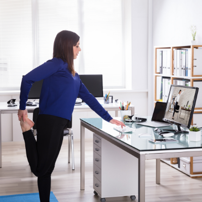 Woman doing leg stretches at her office desk. Stay Healthy While Working From Home - Whole Family Living