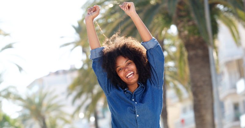 Happy African-American woman with arms raised overhead in joy. Wellness Challenges to Improve Your Health - Whole Family Living